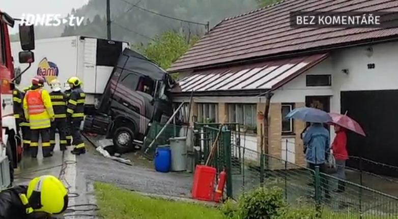 Po střetu s autem zůstal kamion zaklíněný do domu, jeden člověk zemřel